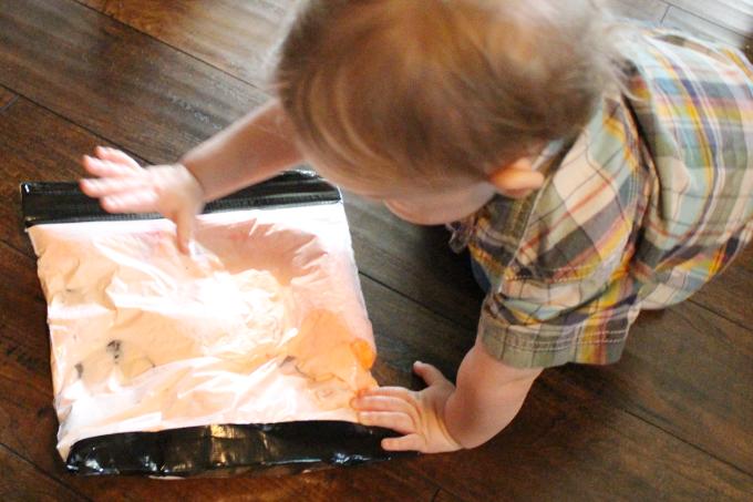 toddler playing with sensory bag