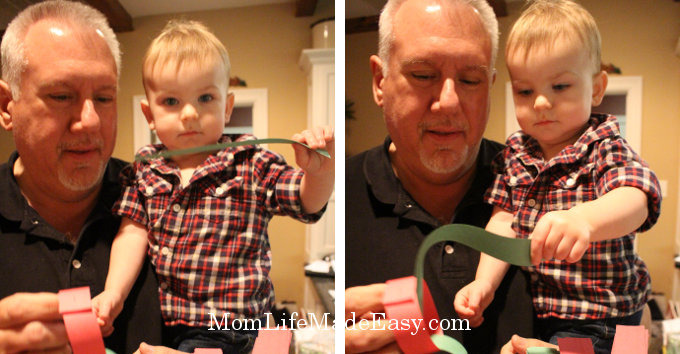 Toddler making paper chains with his grandfather