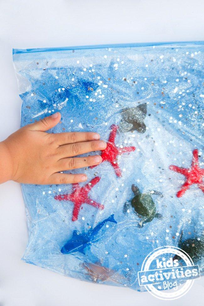 a toddler playing with an ocean sensory bag