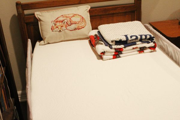 View of organic mattress without sheets - Pillow and blankets folded at the top of the bed.