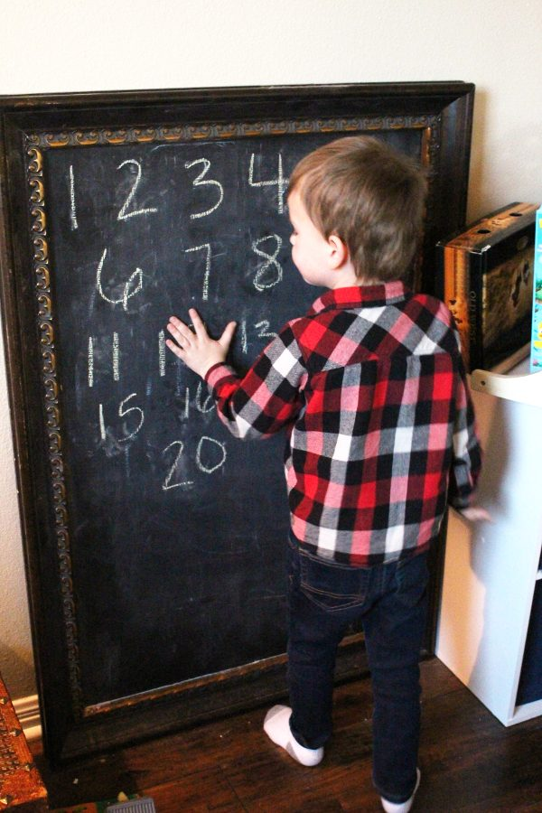young boy playing a learning activity on a chalkboard