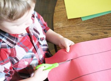 Young boy learning to use scissors