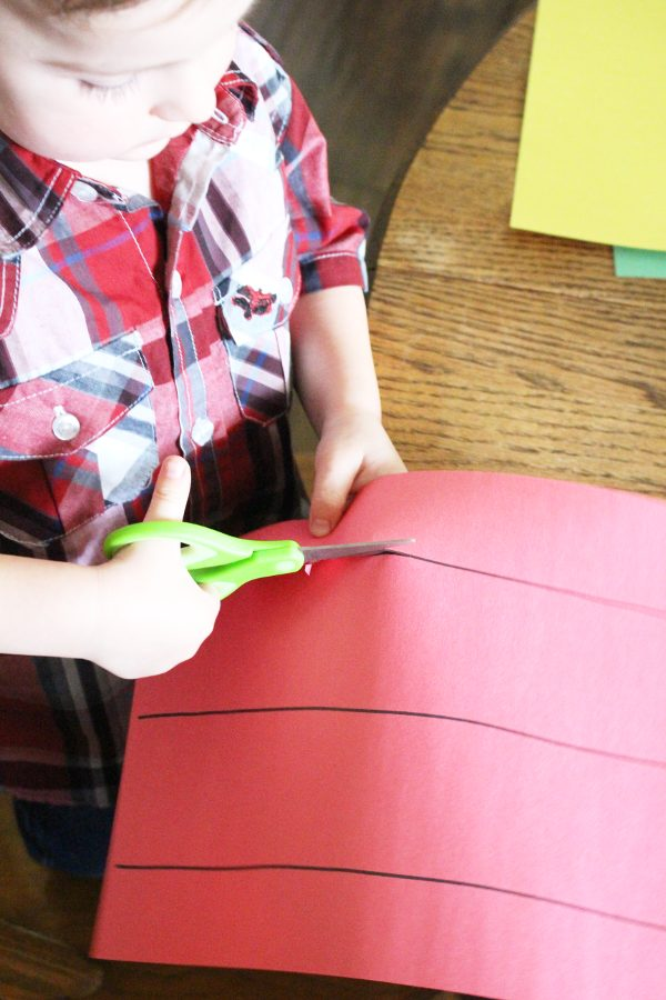 preschool boy using scissors on red construction paper
