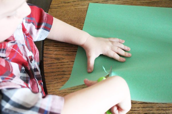 4 year old boy cutting green paper with a pair of scissors