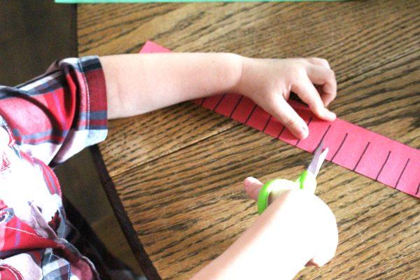 kindergarten student using scissors on construction paper