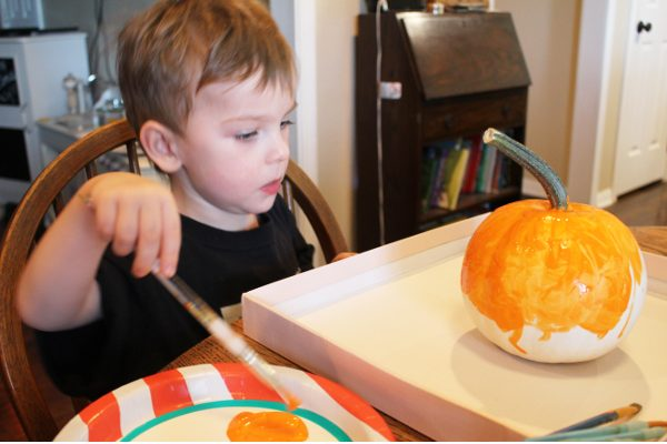 4 year old boy painting a white pumpkin orange