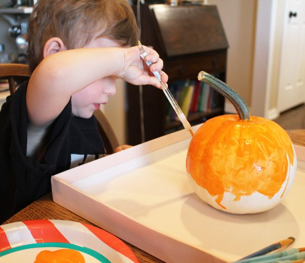 4 year old boy painting a white pumpkin