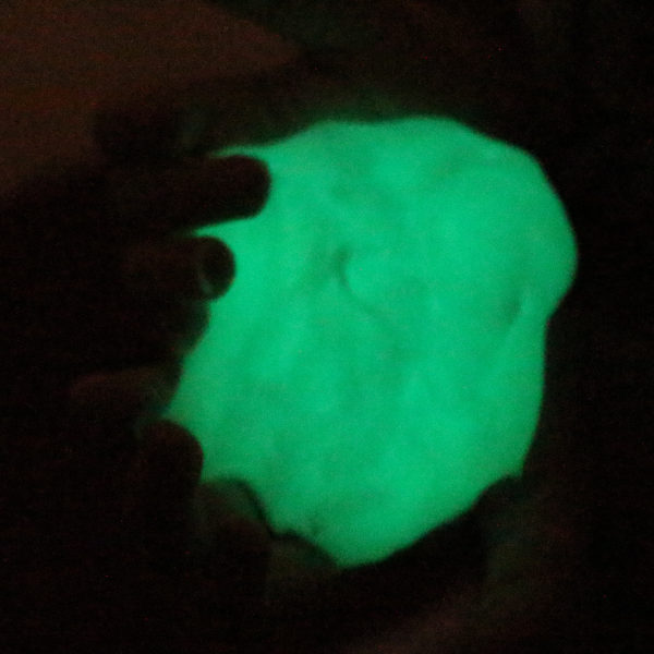 glow in the dark slime glowing in a dark room