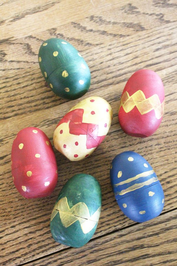 painted wooden easter eggs with stripes and polka dots displayed on a table