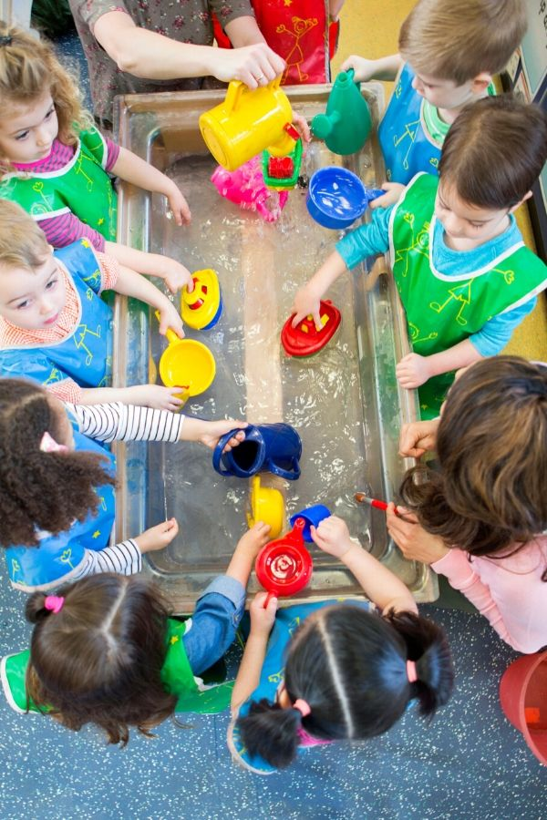 preschool and kindergarten students gathered around a DIY pouring station for water play