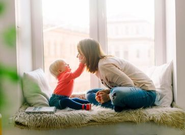 mom and child sitting in window seat playing