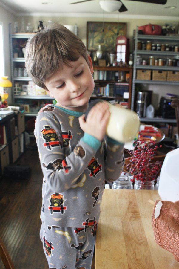 kindergarten student shaking heavy cream learning how to make butter