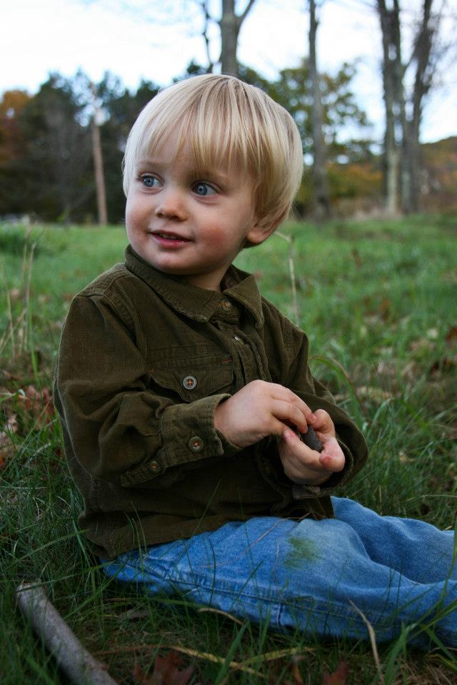Smiling toddler sitting in a field