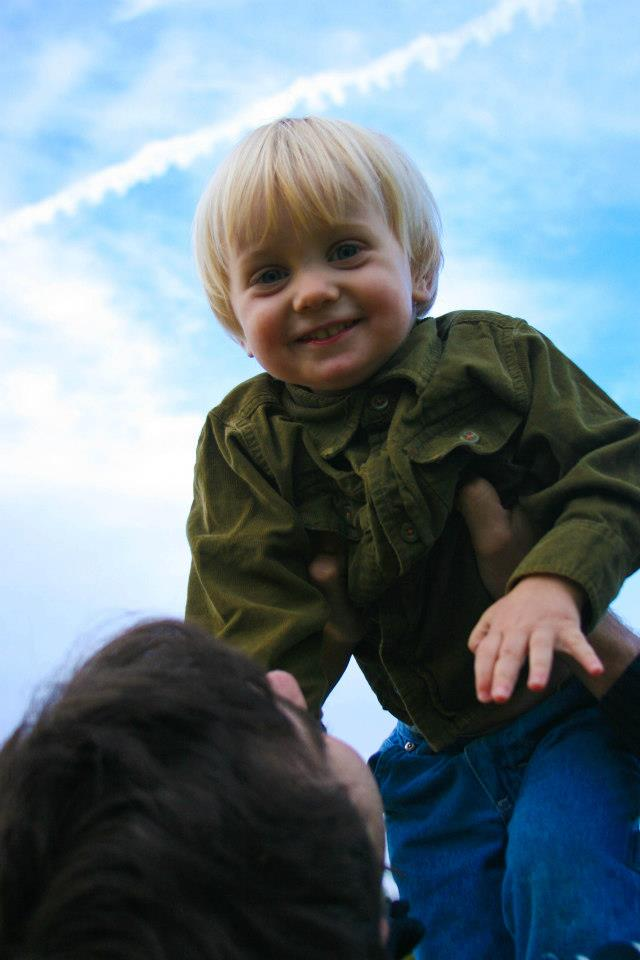 toddler being lifted high in the air by his mother
