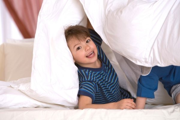 child playing in blanket fort built for if you give a pig a pancake activity