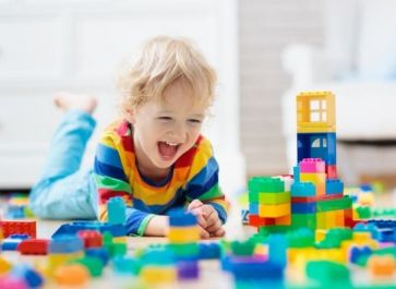 child playing alone with LEGO bricks
