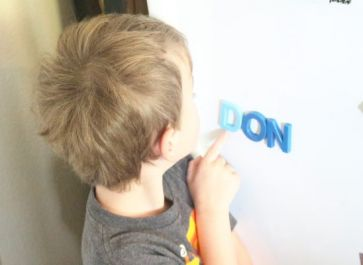 preschool student pointing at letters in alphabet activity