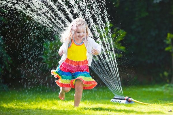 child enjoying a classic yard game of running through the sprinkler in the grass