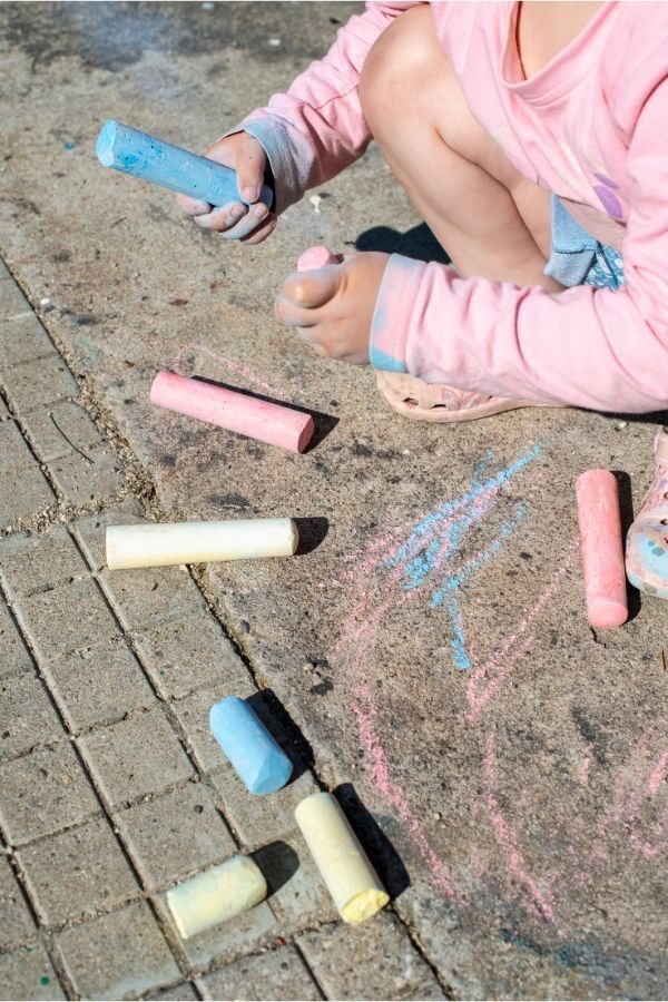 child drawing with chalk is a fun and classic outdoor yard activity