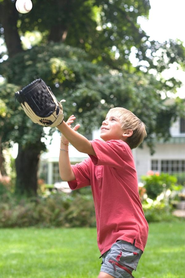 child playing yard game of catch with a ball and mitt