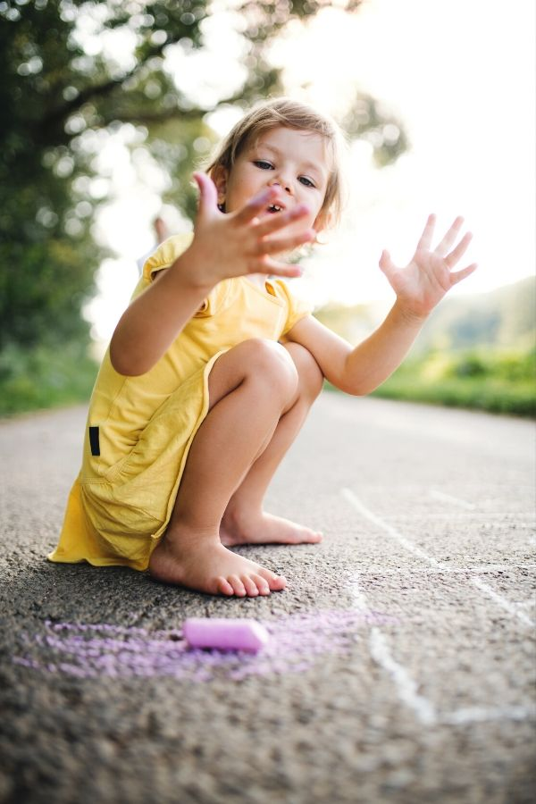 child playing with chalk while enjoying a classic backyard game