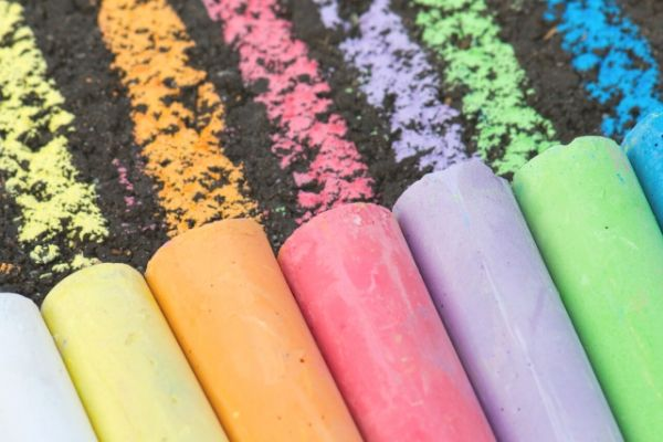 variety of colors of homemade sidewalk chalk drawn on asphalt