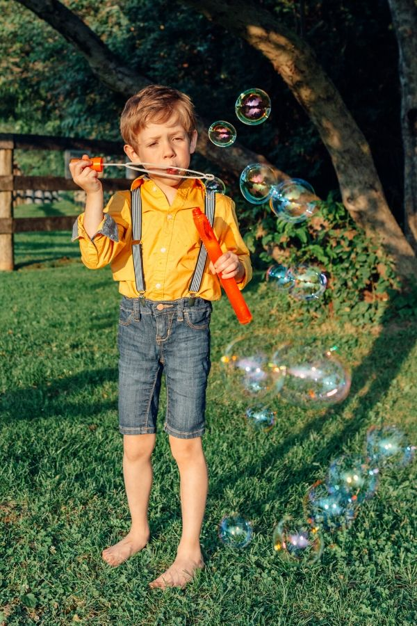 child blowing bubbles with homemade bubble solution recipe