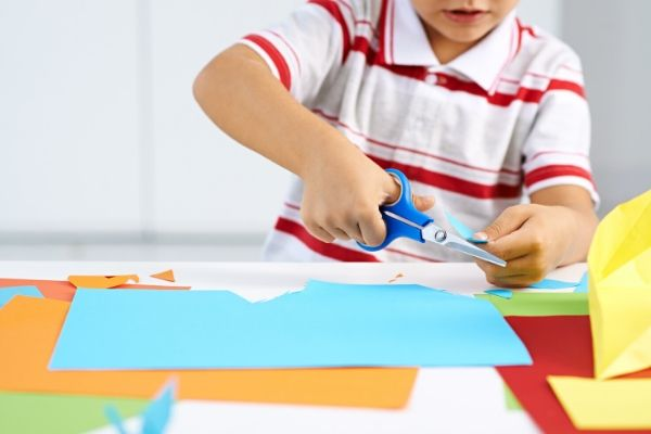 child using scissors and colored paper at his art station