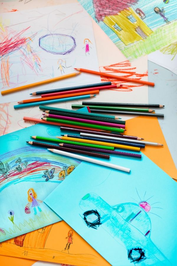 colored pencils, paper displayed together demonstrating the art supplies you will need when setting up an art center for kids