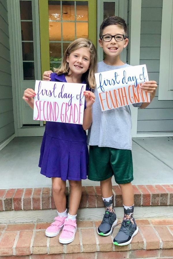 Boy and girl holding first day of school signs for 2nd and 4th grade