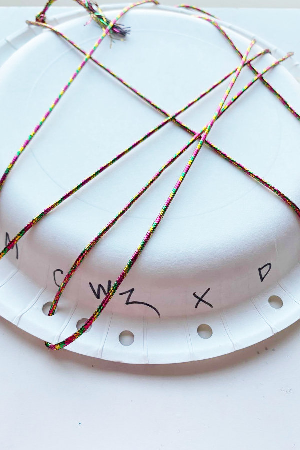 a paper plate laced with string demonstrating the abc lacing cards hack