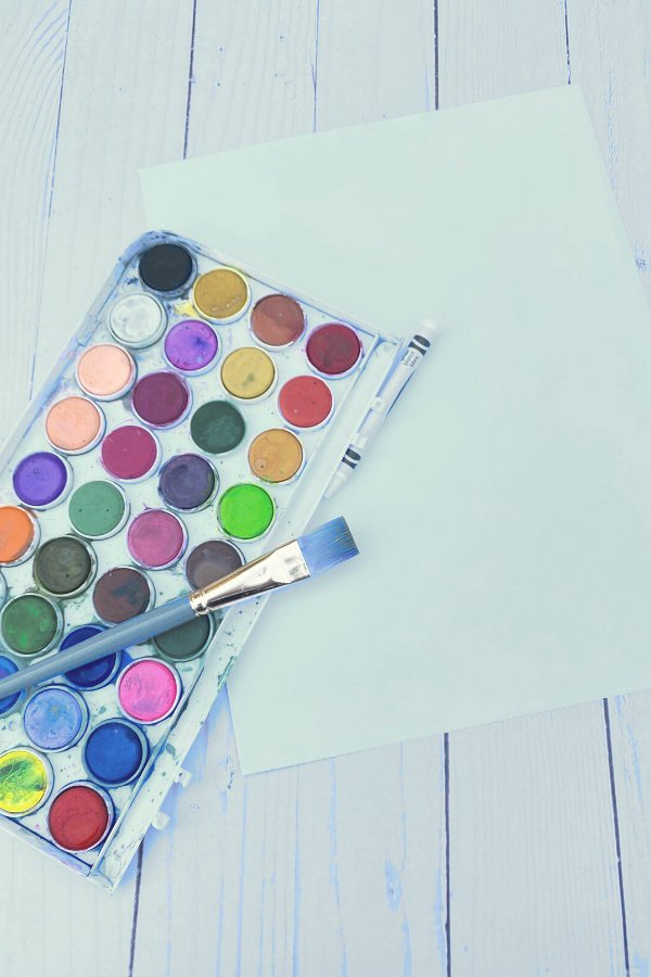 some of the supplies (paintbrush and watercolor palette and paper) needed for crayon and watercolor resist art