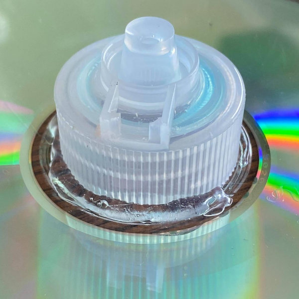 the process of assembling a hovercraft recycling project for kids includes gluing a lid onto a cd