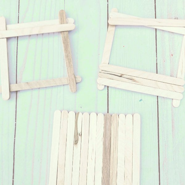 unpainted popsicle stick picture frames on a table