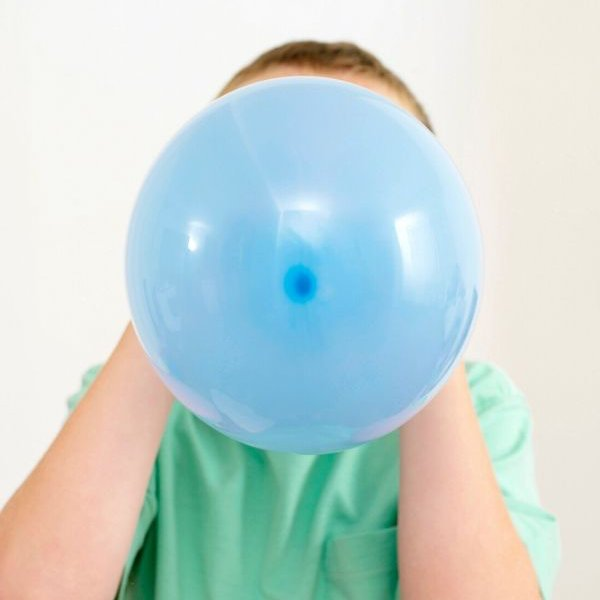 child blowing up balloon for balloon rocket science experiment
