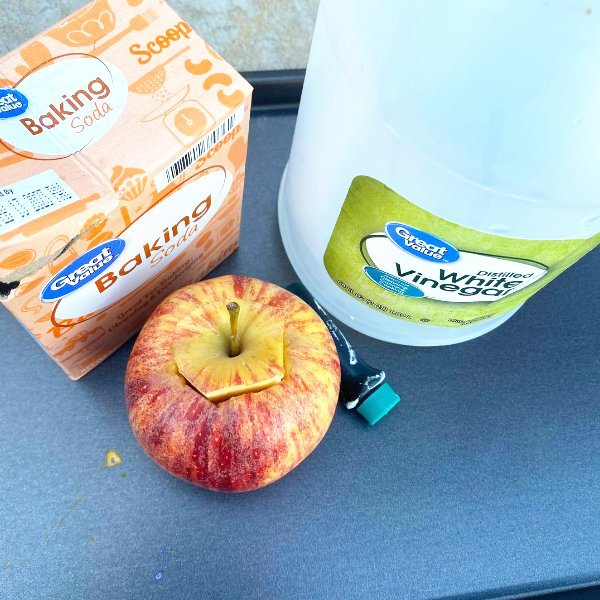 baking soda and vinegar next to an apple to make a very simple volcano science experiment made out of an apple