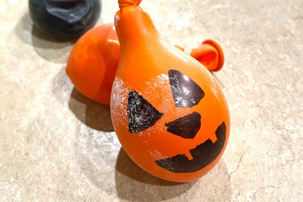 An orange DIY stress ball made to look like a pumpkin