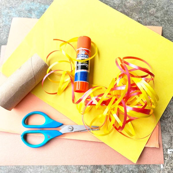 yellow and orange construction paper, ribbon, and glue and scissors, and toilet paper roll gather together to make fall wind sock craft