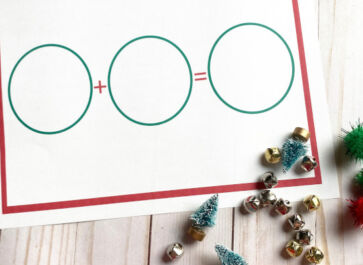 a blank Christmas math worksheet displayed with some jingle bells, mini trees, and red and green pom poms