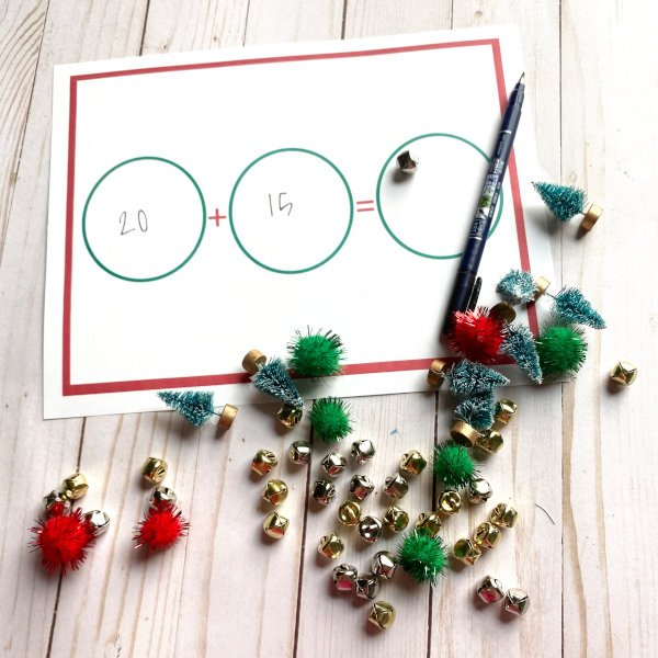 a Christmas math worksheet displayed with some jingle bells, mini trees, and red and green pom poms