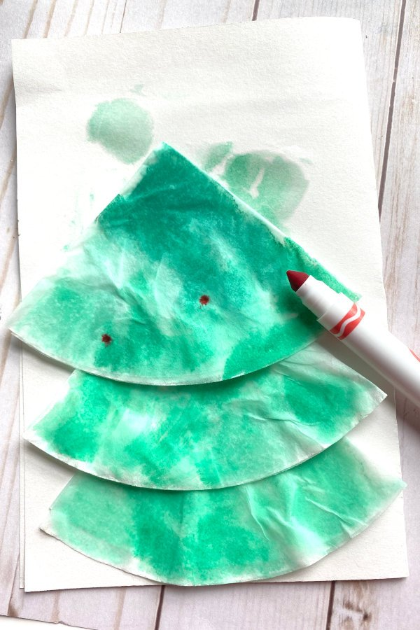 red marker putting dots on coffee filter paper that has been painted green