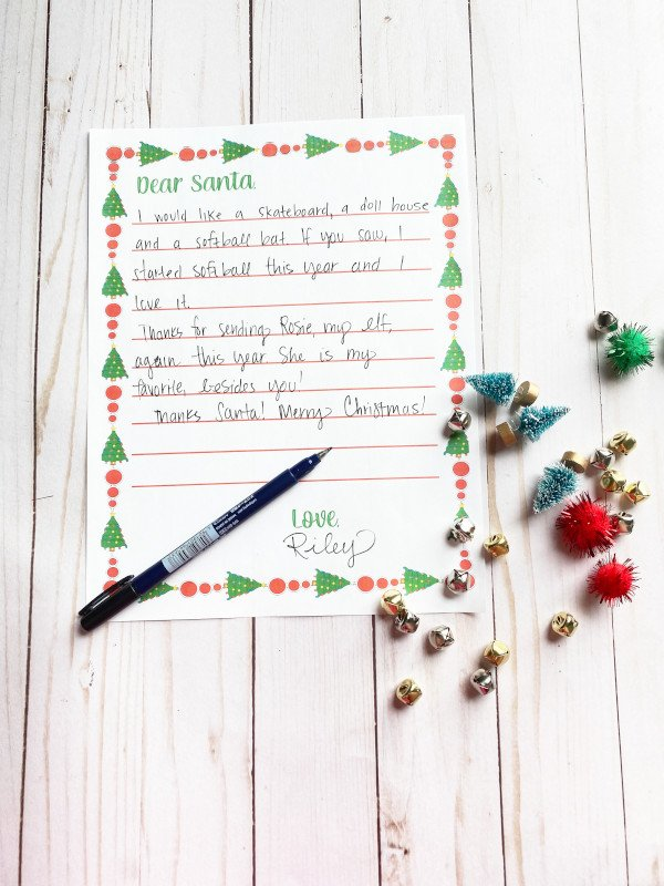 a written on version of the printable santa letter displayed with jingle bells and pompoms