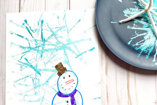 snowflake painting supplies displayed with a finished snowflake painting with a snowman drawing on the same page as the snowflake painting