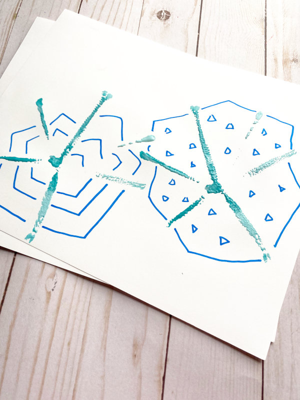 snowflakes drawn around stamped snowflake painting