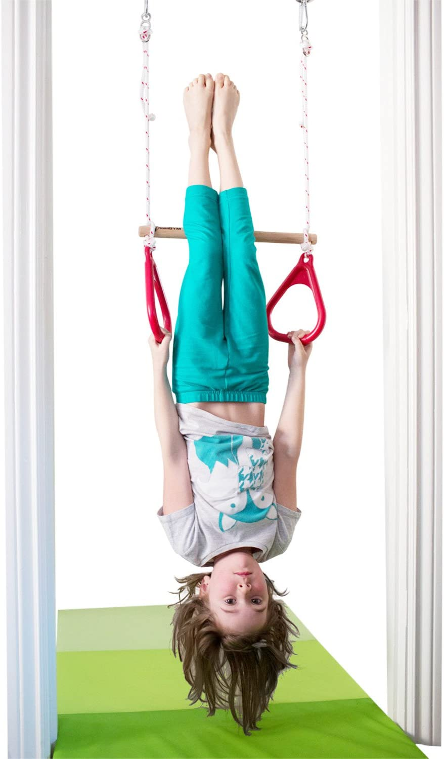 child swinging from an indoor trapeze