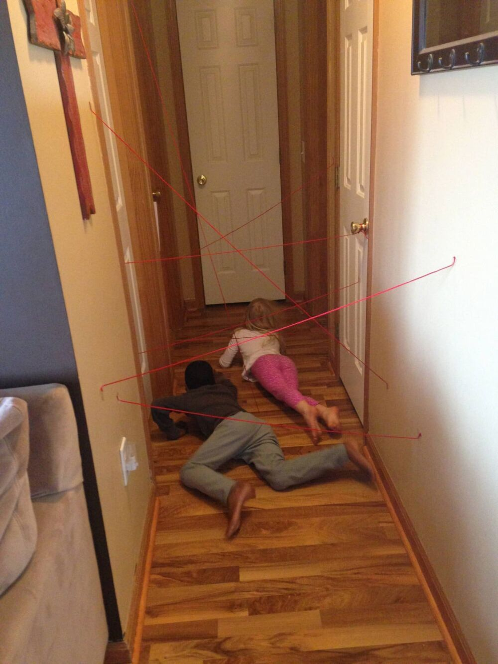 kids finding their way through a maze made out of string taped to the walls of the hallway