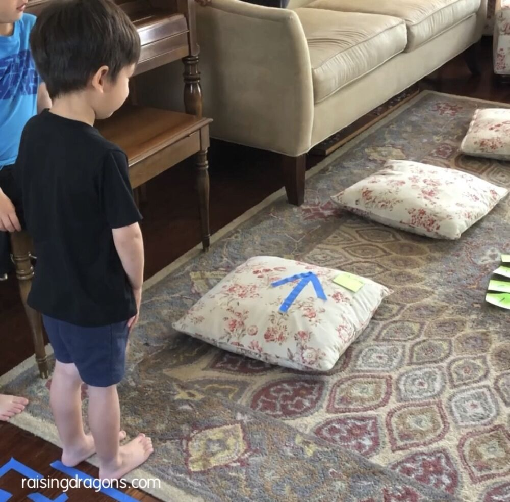 the beginning of an indoor obstacle course with an arrow on a pillow