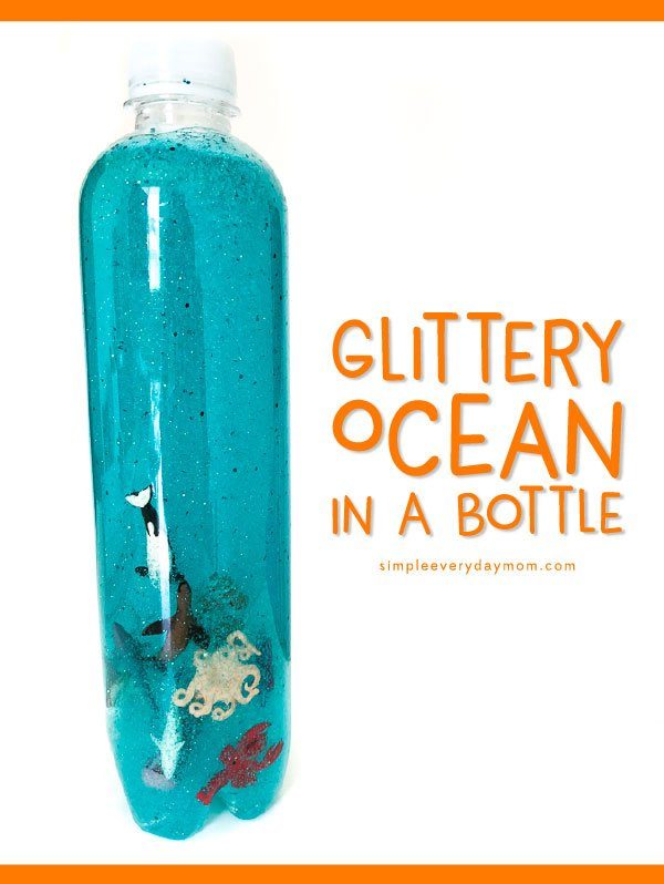 clear bottle beach craft filled with glitter, blue, water, and mini ocean animals