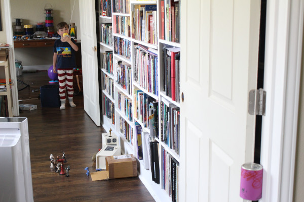 child using one end of the completed tin can phone science project with books in the background
