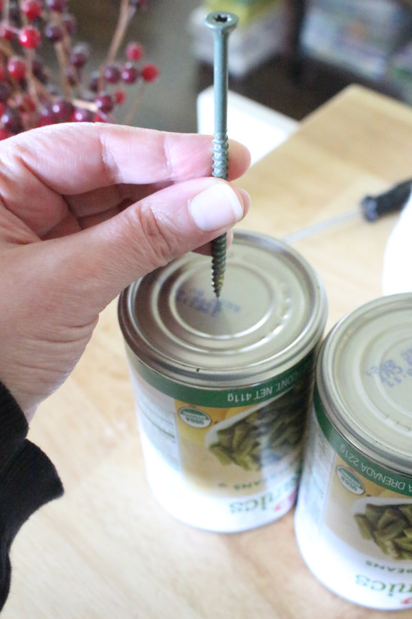 a screw being inserted into a tin can to make a hole
